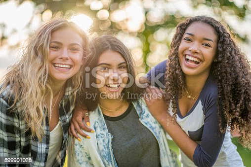 Three teenage girls are outdoors on a summer day. They are all smiling at the camera while the sun sets through the trees behind them.
