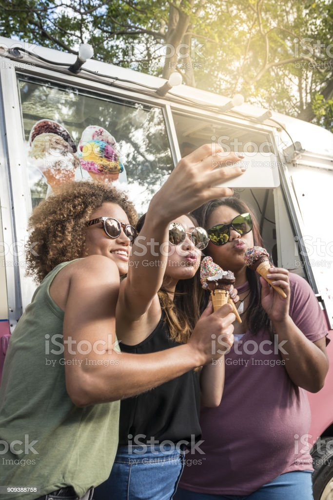 Drie meisjes met ijsjes nemen selfies op ijs bestelwagen, Australië foto