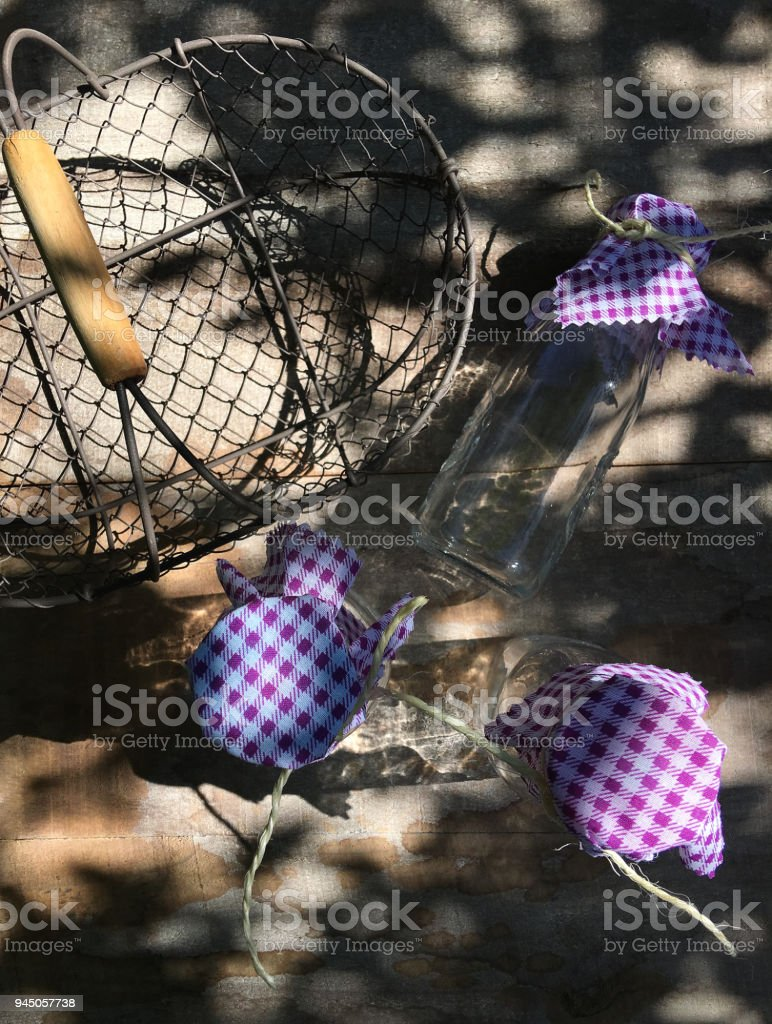 Three glass bottles with purple jute lids and basket on wooden table stock photo
