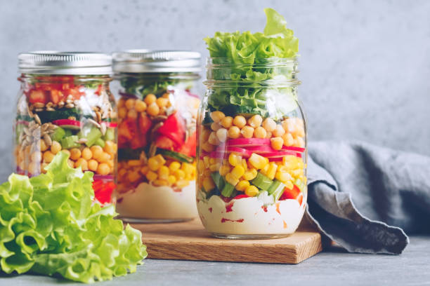 Three glass jars with layering various vegan salads for healthy lunch. The concept of fitness and vegetarian food. stock photo