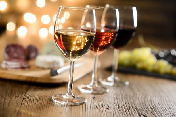레드 와인, 로즈 와인, 화이트와 와인 3 잔 프랑스 치즈와 낭만적인 희미 한 빛과 아늑한 분위기 레스토랑 나무 테이블에서 조제 - wine 뉴스 사진 이미지
