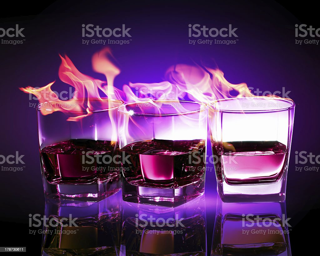 Three glasses of burning purple absinthe royalty-free stock photo
