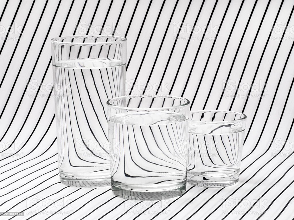 Three glasses of drinking water on striped tablecloth stock photo