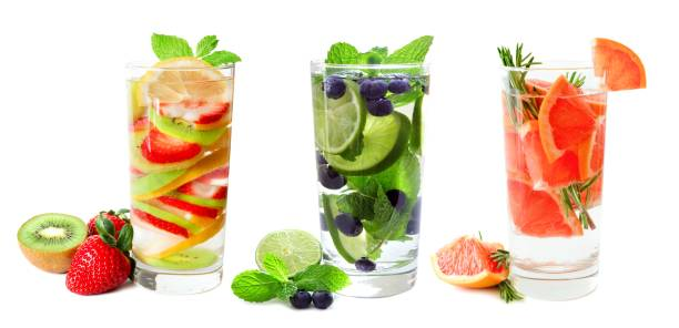 three glasses of fruit infused water isolated on white - infusion pamplemousse photos et images de collection