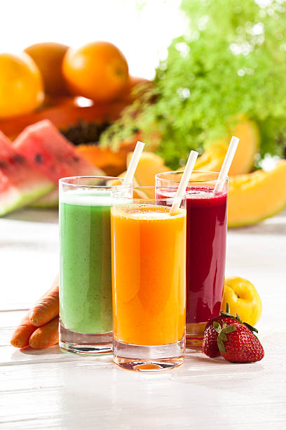 Three glasses of fruit juice with fruits in the background Three Glasses of Fruit Juices on White Garden Table. vegetable juice stock pictures, royalty-free photos & images