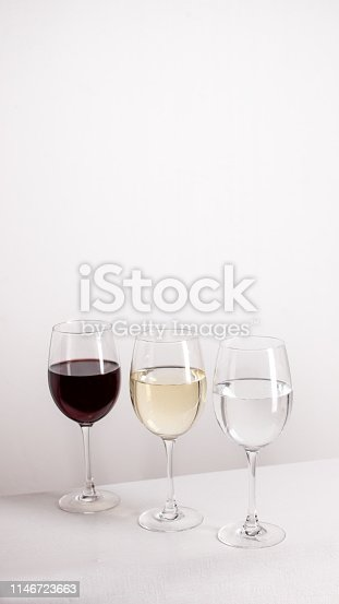 924487256 istock photo Three glasses of red, white wine and water standing in one line on grey background. 1146723663