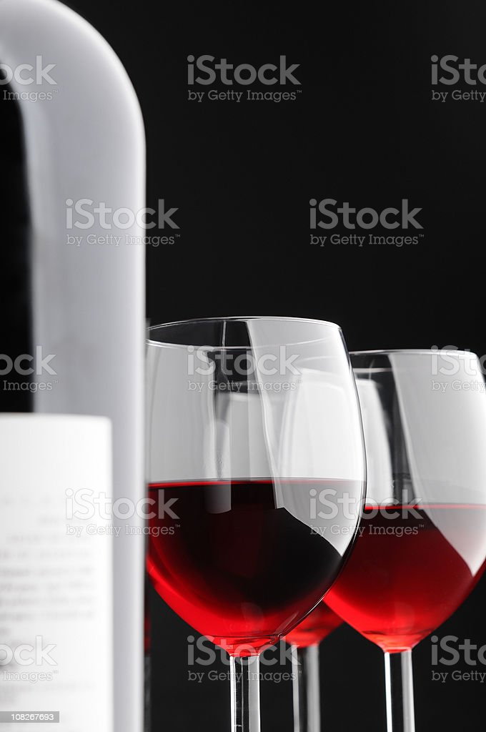 Three Glasses of Red Wine and Bottle on Black Background royalty-free stock photo