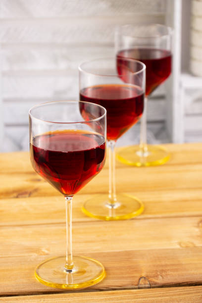 Three glasses of red wine on a wooden background. Shallow depth of field. Blurred background stock photo