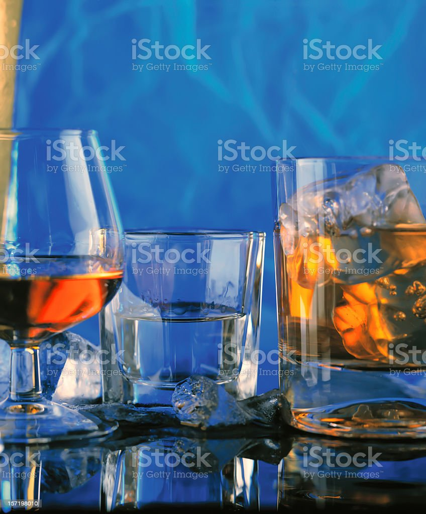 Three glasses with hard alcohol drinks, reflected in the table. royalty-free stock photo