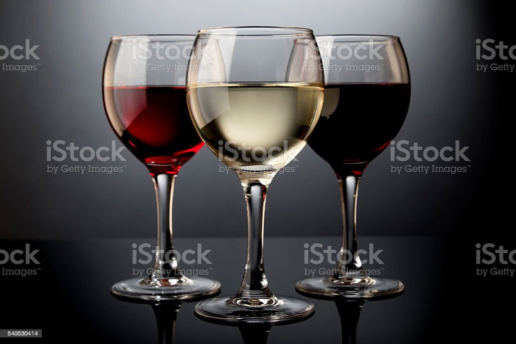 Three glasses with red, rose and white wine stock photo