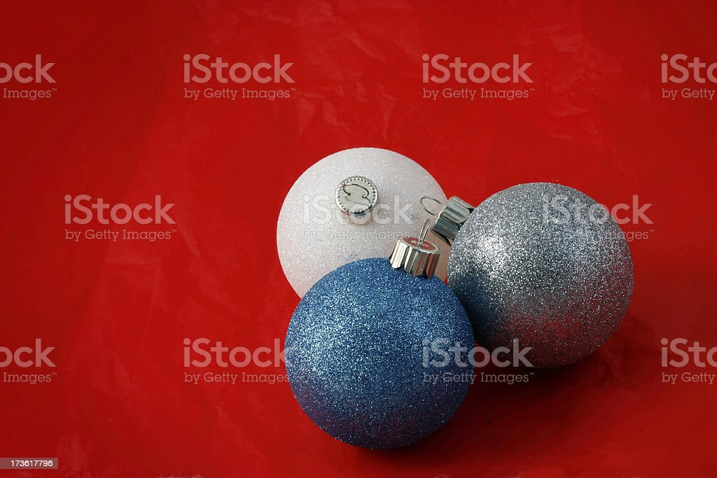 Three Glitter Chirstmas ornaments on red background stock photo
