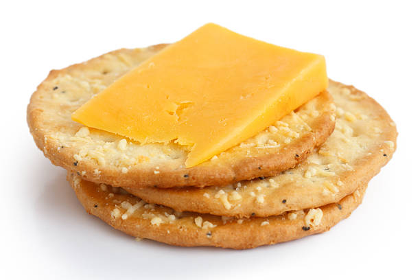 Three golden cheese crackers with cheese on white background stock photo
