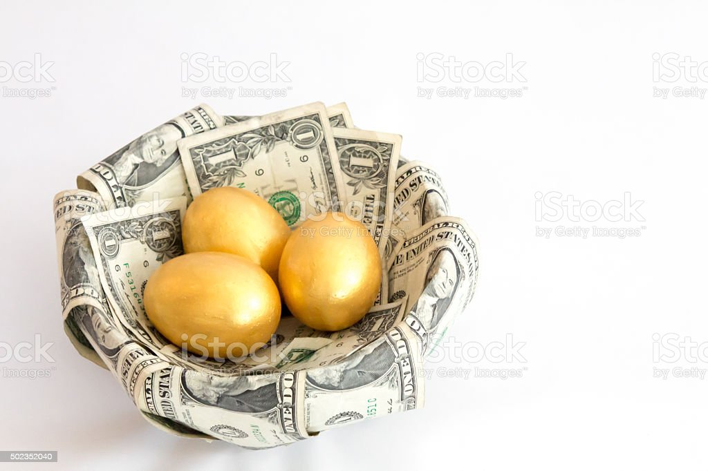 Three golden eggs in a nest made from dollars stock photo
