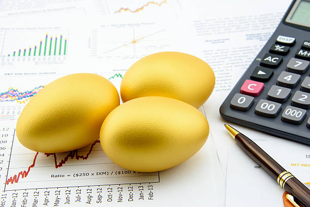 Three golden eggs with a calculator on financial reports. Three golden eggs with a calculator on business and financial reports : Investment concept debenture stock pictures, royalty-free photos & images