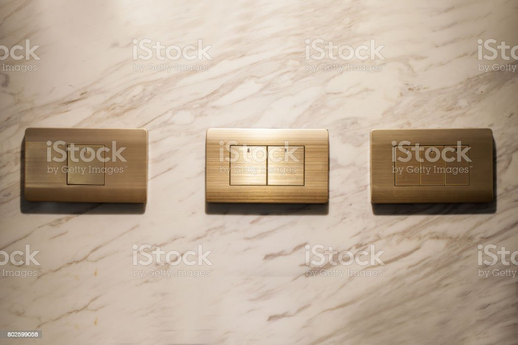 Three golden lighting switchs on wall, on and off stock photo