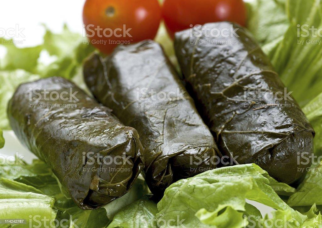 Three Greek dolmades resting on a lettuce leaf stock photo