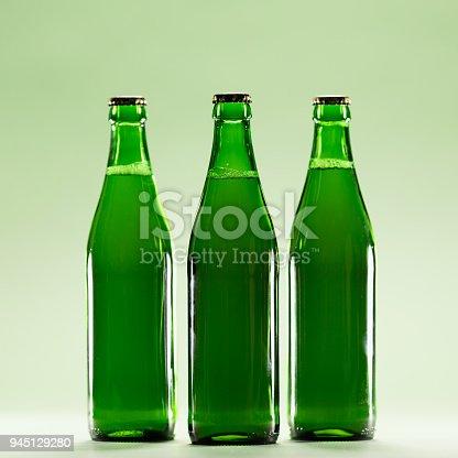 istock Three green bottles on a light green background. 945129280