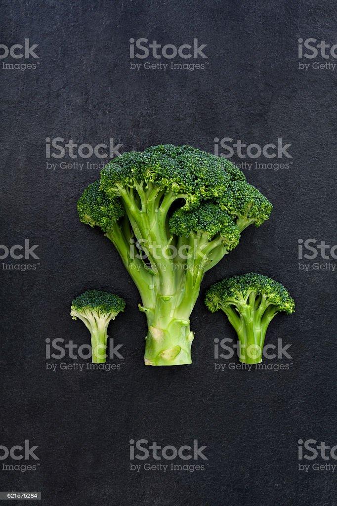 Three green broccoli on dark gray slate background photo libre de droits