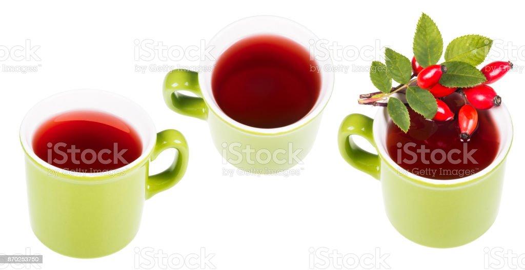 Three green mugs with hot medicinal tea from rose hips stock photo