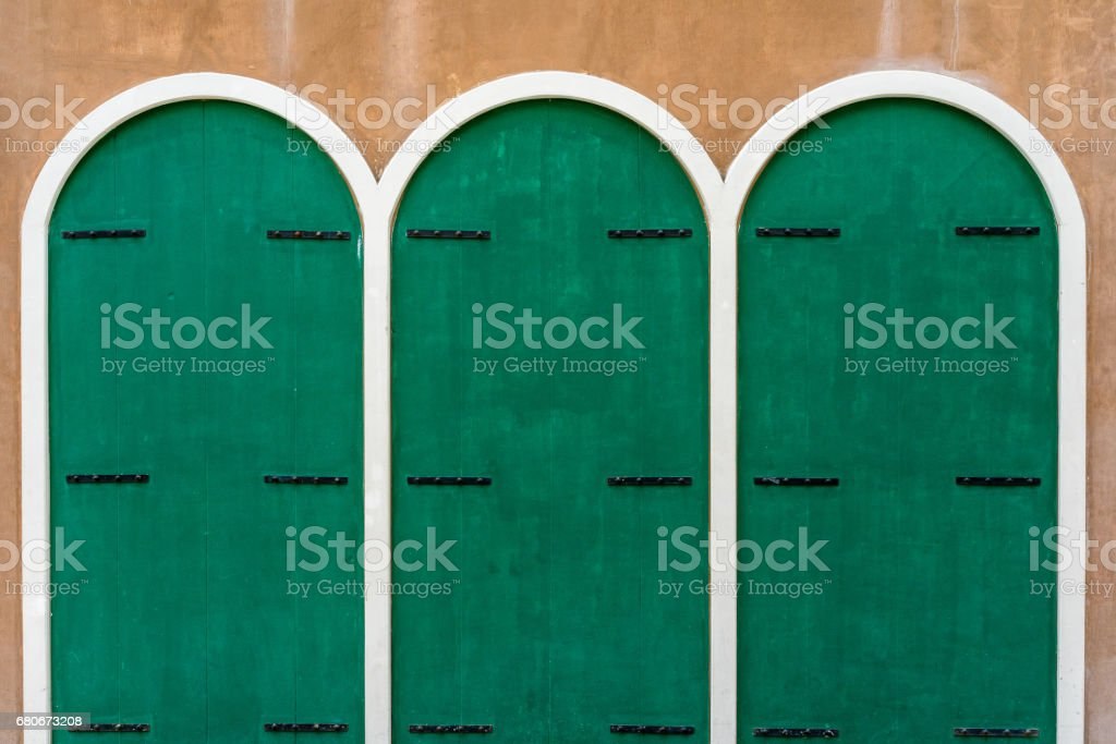 Three green wooden doors on brown concrete wall stock photo