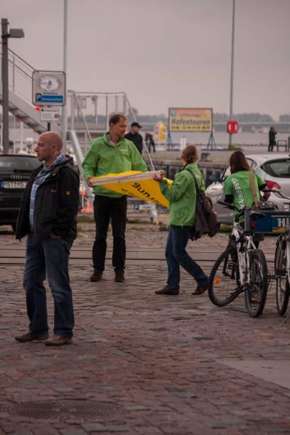 drei greenpeace aktivisten mit dem gelben banner - merkel cdu stock-fotos und bilder