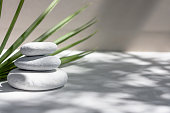 istock Three grey roundstones and bath towels on white background with green leaves. Spa stones, zen like concept. 1223589056