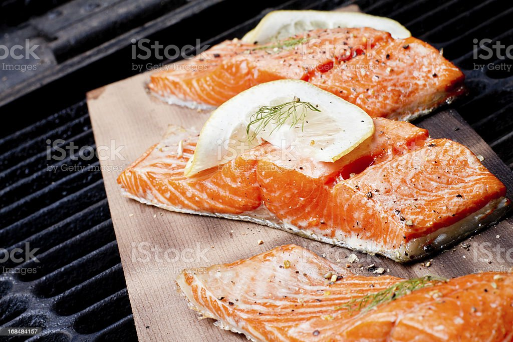 Three Grilled Salmon Filets on Cedar Plank Three wild-caught salmon filets on a cedar plank in a backyard grill.  Fist is bright reddish orange and is topped with lemon, dill and cracked pepper file_thumbview_approve.php?size=1&id=19631280 Barbecue - Meal Stock Photo