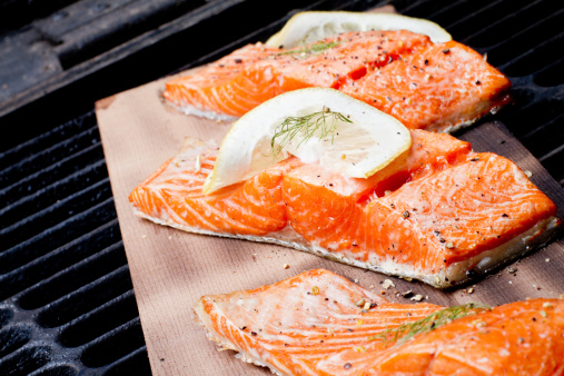 Three Grilled Salmon Filets On Cedar Plank Stock Photo - Download Image Now
