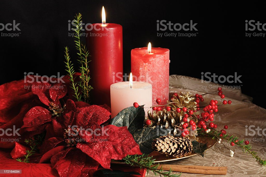 Three grouped Christmas candles standing among garlands stock photo