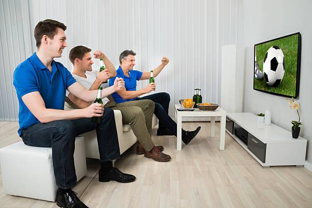 drei männer beobachten fußballspiel - fußball themenzimmer stock-fotos und bilder