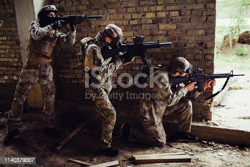 istock Three guys in ammunition are standing and hiding behind wall. First man is siting on his knees and targeting. Other guys are standing behind each other. They have rifles in therir hands. 1140379007