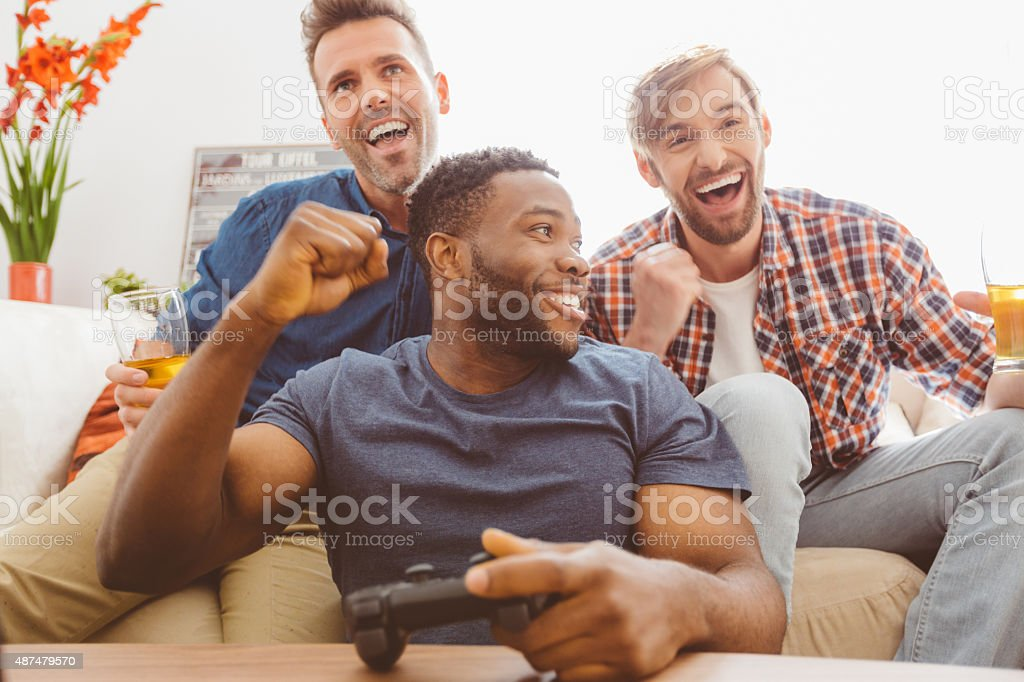 Three guys playing video games stock photo