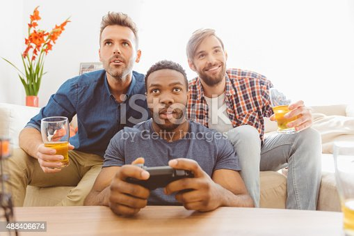Multi ethnic - caucasian and afro american - friends sitting on sofa at home, playing video games, drinking beer. Close up of faces.