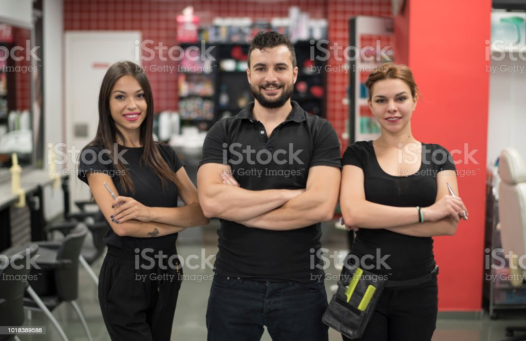 Three hairdressers posing in barber shop stock photo