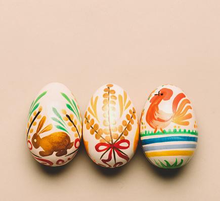 Three handmade Easter eggs on creamy background. Folk traditions. Slavic holiday.