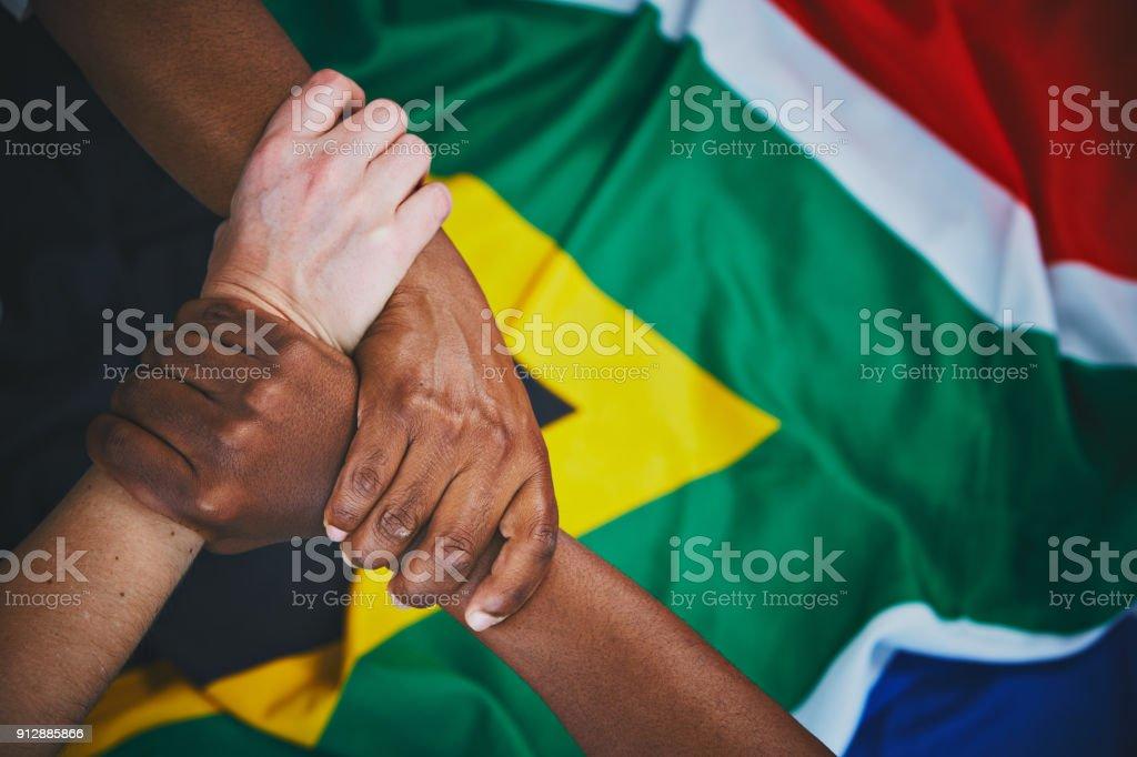 Três mãos entrelaçadas em unidade bandeira sul-africana - foto de acervo