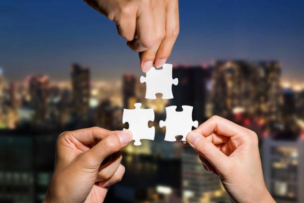 drei hände halten stück puzzles auf stadtbild hintergrund. business-partnerschaft-konzept. business-matching. - dinge die zusammenpassen stock-fotos und bilder