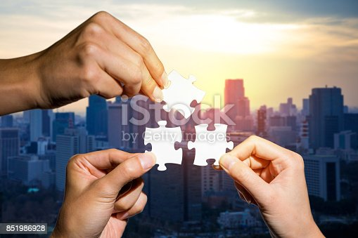 istock three hands holding piece of jigsaw puzzle on cityscape background. business partnership concept. business matching. 851986928