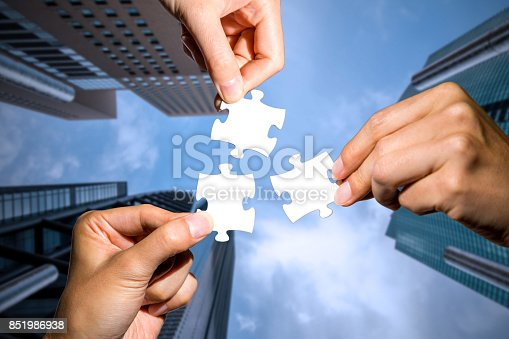 istock three hands holding piece of jigsaw puzzle on cityscape background. business partnership concept. business matching. 851986938