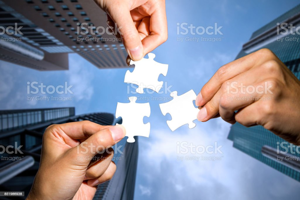 three hands holding piece of jigsaw puzzle on cityscape background. business partnership concept. business matching. stock photo
