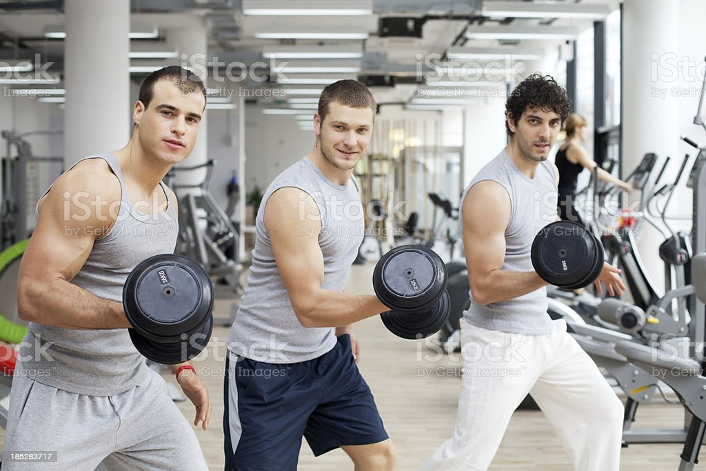 Three handsome men exercising with weights in gym. royalty-free stock photo