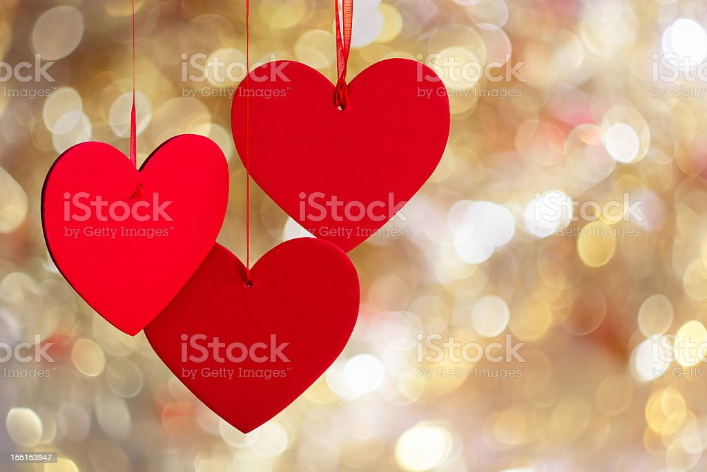 Three hanging red hearts on defocused light background. stock photo