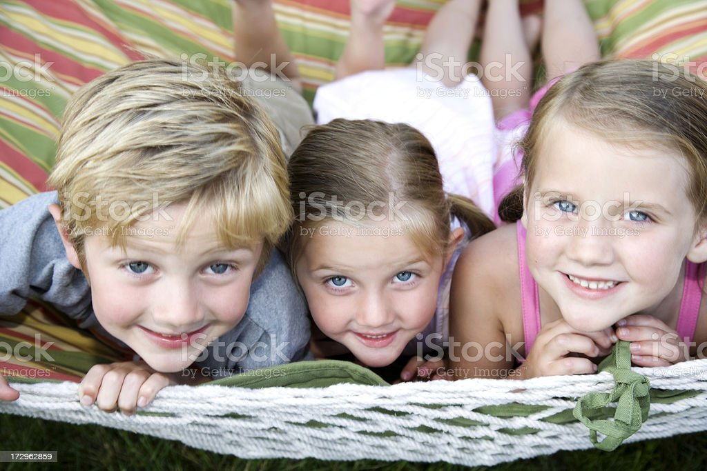 Three happy adorable children playing outside stock photo