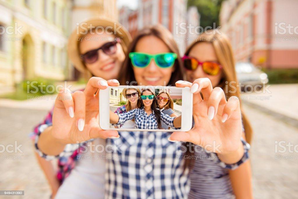 Three happy best girlfriends in glasses making selfie on smartphone royalty-free stock photo