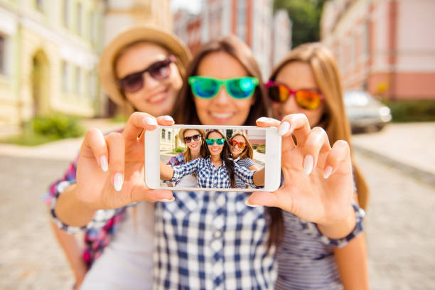 Three happy best girlfriends in glasses making selfie on smartphone stock photo