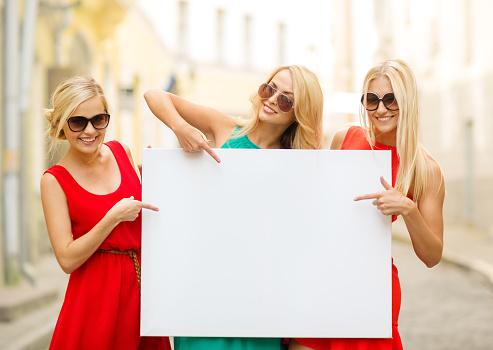 istock three happy blonde women with blank white board 481325906