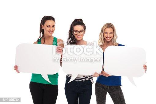istock three happy casual women holding blank speech bubbles boards 640195764