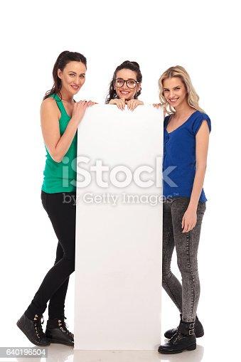 istock three happy casual women presenting a big blank board 640196504