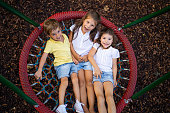 three happy laughing children one boy and two girls preschool age laying in net swing of playground looking up smiling at camera