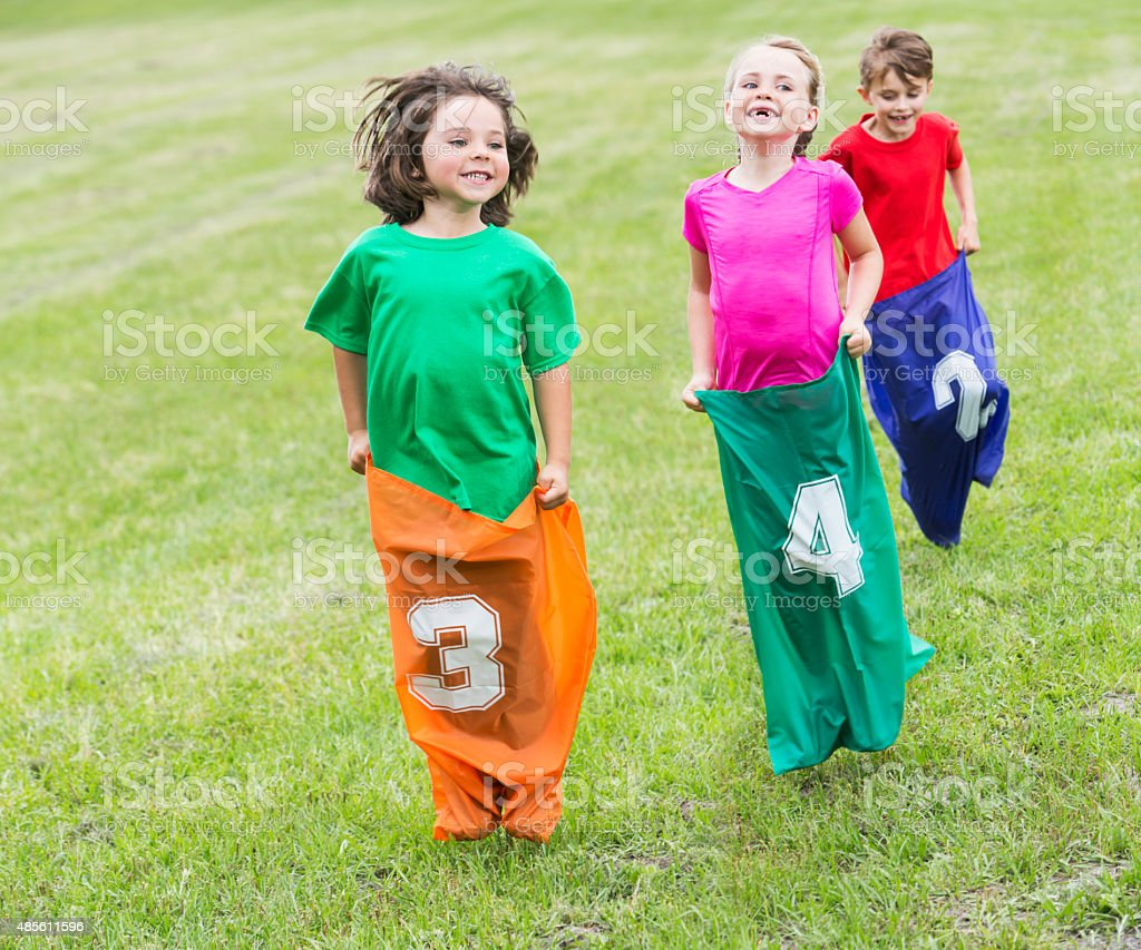 Three happy children in potato sack race stock photo